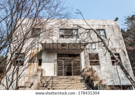 The concrete exterior of an old abandoned mental hospital. - stock photo