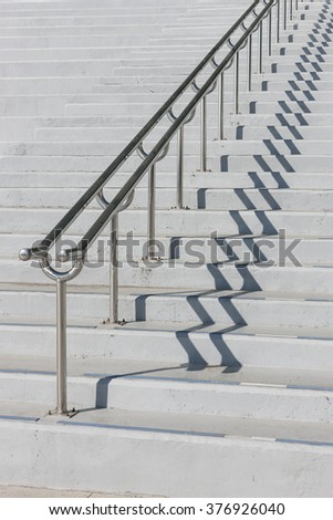 The concrete stair and handrail(banister) shadow in a public park(outdoor, exhibition, convention, play ground, stadium, arena) at the daylight.
