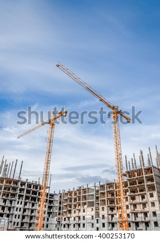 the construction crane and the building against the blue sky - stock photo