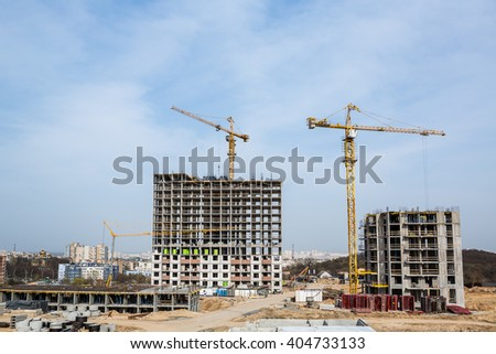 The construction crane and the building against the blue sky. Construction site with crane and building. Big construction crane and the building against the sky background.