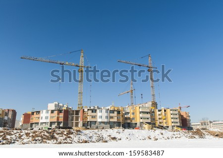 The construction of new residential buildings in Moscow on a background of a winter landscape.