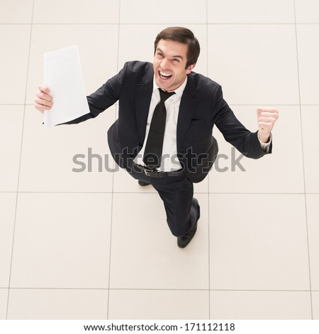 The contract is mine! Top view of excited young man in formalwear holding a paper in one hand and gesturing - stock photo