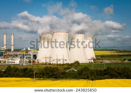 the cooling stacks in power station Pocerady, with rape field - stock photo