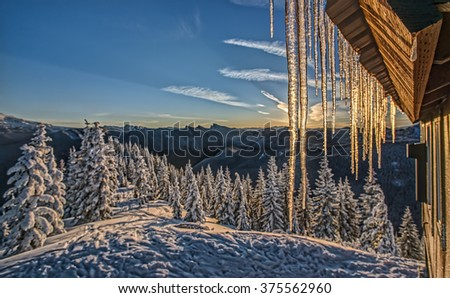 The Corner of an Alpine Snow Hut Drips with Icicles that Glow with the Morning Sunrise in the Cascade Mountains - stock photo