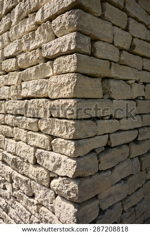 The corner of an old stone house in the Luberon area of Provence, France showing the contrast of one wall in bright sun and the other in deep shade. - stock photo