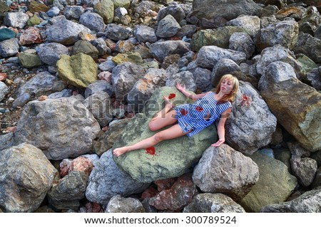The corpse of a young girl on the rocks  - stock photo