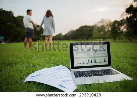 The couple checking reported profits in the garden. - stock photo
