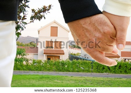 the couple holding hands with houses in the background - stock photo