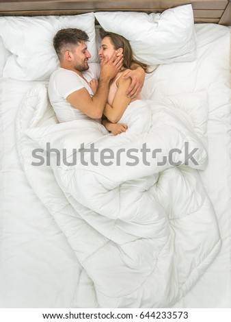 The couple kiss in the white linens. View from above