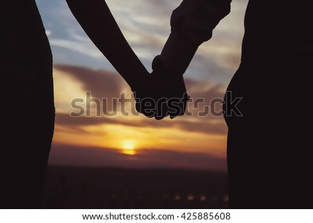 The couple that hold each other's hand watch the sunset. The sun is sinking. Cloudy and blue sky. Photo of close-ups and silhouette. - stock photo