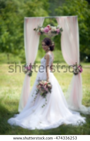 the couple with a bouquet of flowers near the wedding arch for outdoor ceremony on a background of green trees