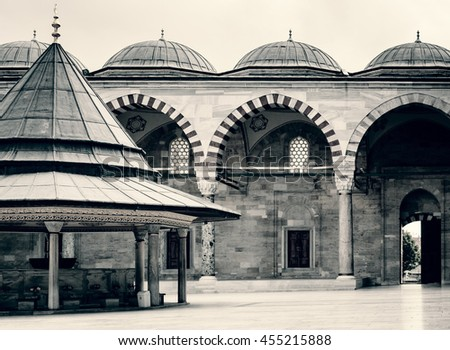 The courtyard with fountain inside of Fatih Mosque, landmarks of islamic culture of Istanbul. Traditional turkish Mosque in old town. Arabic architecture in Turkey, retro style photo. - stock photo