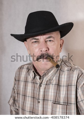 The cowboy with mustache, in a black hat smoking a cigar - stock photo
