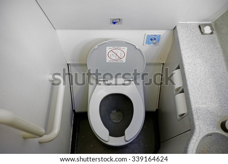 The cramped and dirty bathroom of a commercial airliner.         - stock photo