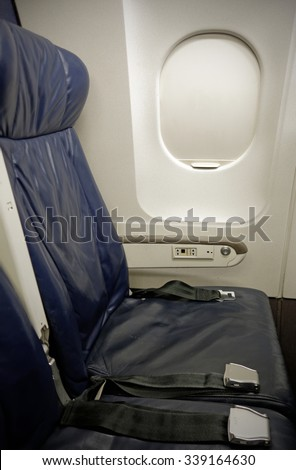 The cramped seating of the coach section of a commercial airliner. - stock photo