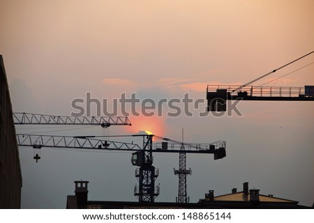 The crane machine silhouettes at sunset in summer