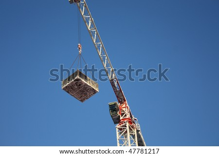 The crane picking up heavy loading and blue sky - stock photo