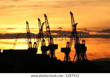The cranes of a Clyde shipyard silhouetted by a Glasgow sunset - stock photo