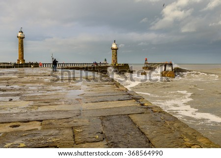 The crashing waves of a winters tide on the north coast of Great Britain from the North Sea at the harbour entrance to the historic fishing town of Whitby. - stock photo