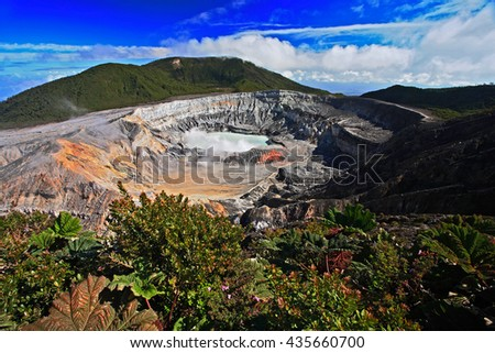 The crater and the lake of the Poas volcano in Costa Rica. Volcano landscape from Costa Rica. Active volcano with blue sky with clouds. Hot lake in the crater Poas. Volcano in Costa Rica.  - stock photo