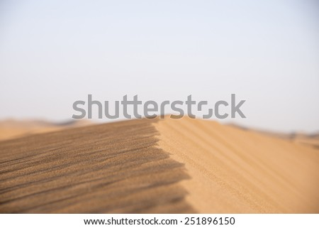 The crest of a sand dune in the Sahara desert in Erg Chegaga in Morocco in the spring during a hot sunny day. - stock photo