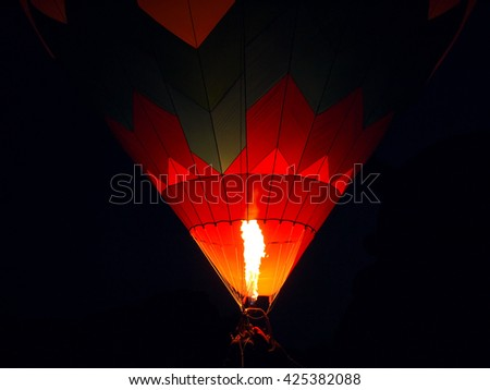 The crew, basket, flame, and ropes of a hot air balloon against a dark, blue black night sky. - stock photo