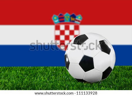 The Croatian flag and soccer ball on the green grass