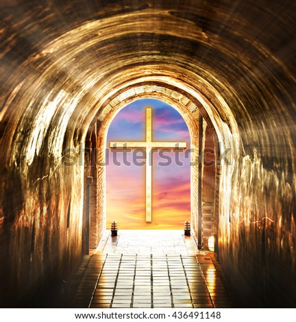 The cross against the sunset sky at the end of tunnel. - stock photo