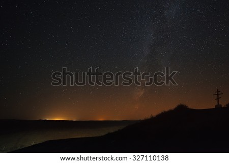 The cross on the background of the Milky Way in the night sky. - stock photo