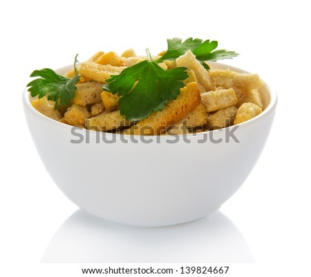 The croutons decorated with parsley in a cup, isolated on white