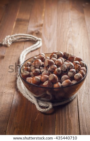 The crude hazelnut in translucent plate with a rope on a table with a wooden background. Vertical frame. Healthy food.
