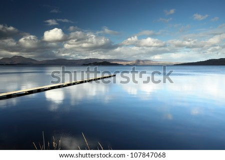 The Cruin jetty and cloud reflections on the shore of Loch Lomond, Scotland - stock photo