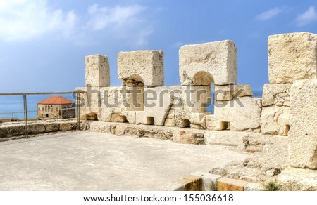 The crusaders' castle in the historic city of Byblos in Lebanon. A view of the battlement from the top of the castle and the traditional lebanese house in the background - stock photo