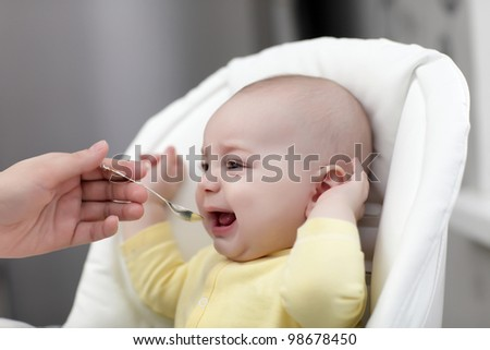 The crying baby with spoon food at home - stock photo