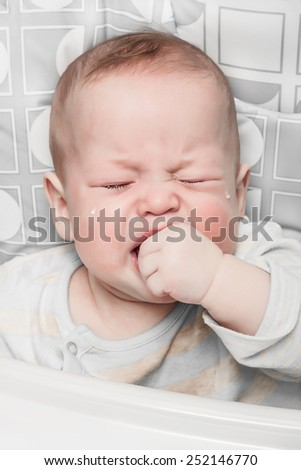 The crying boy in tears, hand in mouth, on  white background - stock photo