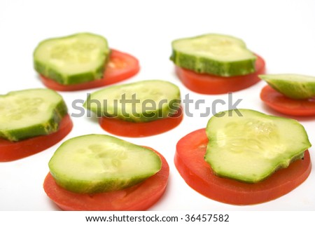 The cucumber and tomato are cut by slices isolated on white. Snack for vegetarians