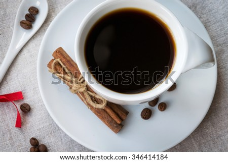 the cup of black aromatic coffee, coffee beans in shape of heart, spices