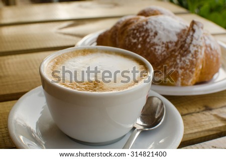 The cup of cappuccino with croissant in the background - the tipical italian breackfast.