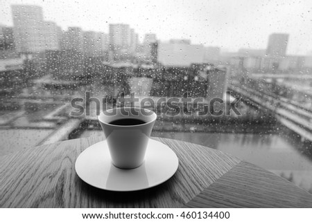 The cup of coffee on a rainy day window background.