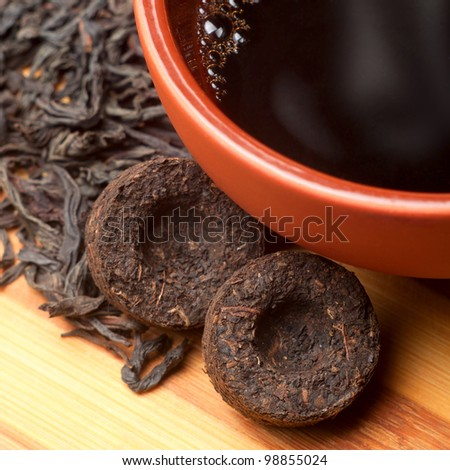 The cup of pu_erh old aroma tea and dry cylindrical bricks - stock photo