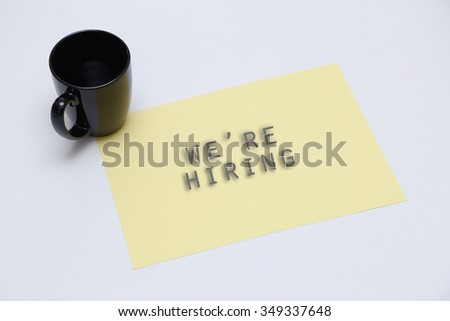 The cup & yellow paper with word we're hiring . blur effect - stock photo