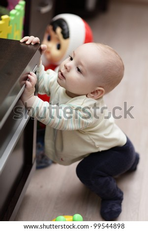 The curious kid mounting on a cupboard at home - stock photo