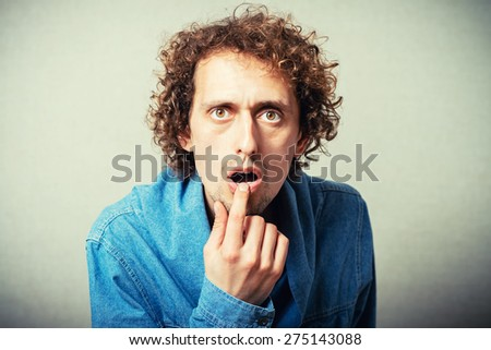 The curly-haired man finger in his mouth, a gesture of surprise. On a gray background. - stock photo