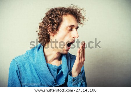 The curly-haired man yawning gesture. On a gray background. - stock photo