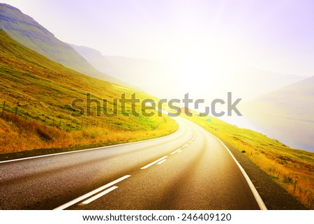 The curve of the road in the mountains. The Faroe Islands. Sunset - stock photo