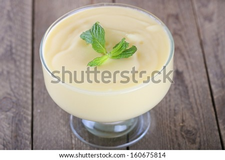 The custard  in  a glass on wooden table - stock photo