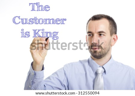 The Customer is King - Young businessman writing blue text on transparent surface