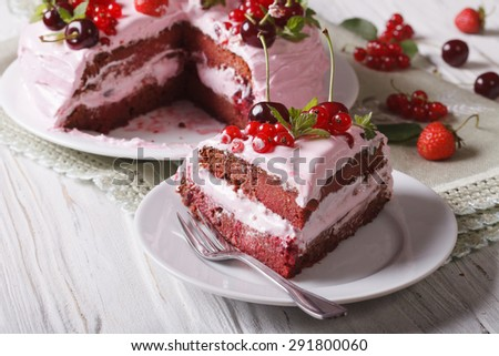 The cut piece of berry cake with pink cream on a plate close-up. horizontal