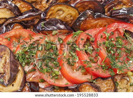 The cut slices of tomato and eggplants for snack