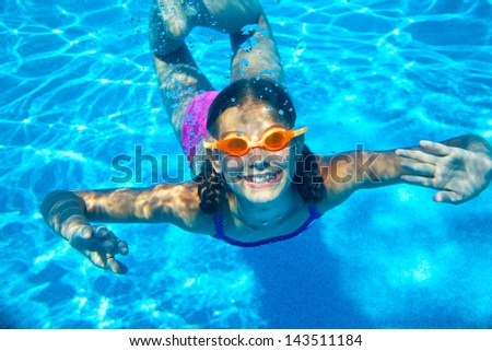 The cute girl swimming underwater and smiling - stock photo
